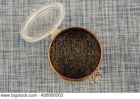 Flat Lay Open Tea Coffee Tin With Latch. Latch Lock Tin With Dried Tea Leaves. Sele