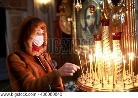 Woman In Protective Mask With Candle In Church