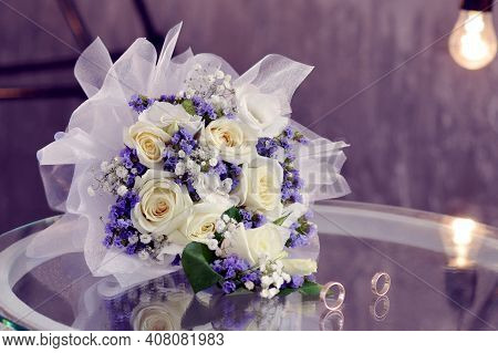 Wedding Bouquet Of White Roses, Rings, Purple Dry Little Flowers. Delicate White Roses, Purple Flowe