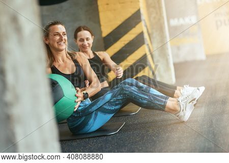Two Young Happy Athletic Women In Sportswear Exercising With Fitness Ball At Gym, Working Out Togeth