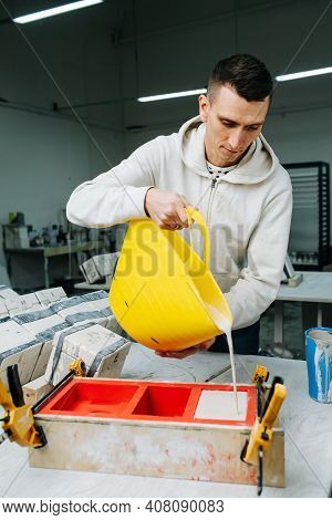 Man Pouring Gypsum Plaster In Open Form For Mold Casting For Making Tableware.
