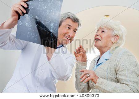 Doctor hombre maduro feliz con la mirada paciente femenino senior en rayos x