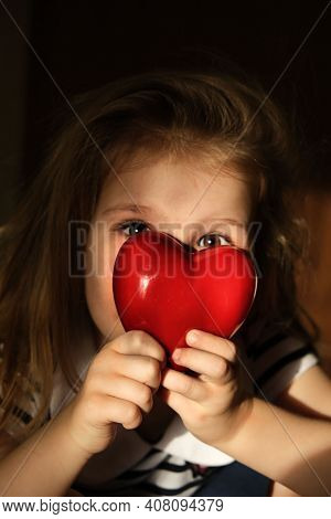 Defocused Little Girl With Red Heart At Home, The Rays Of The Morning Sun Soft Illuminate Dark Room