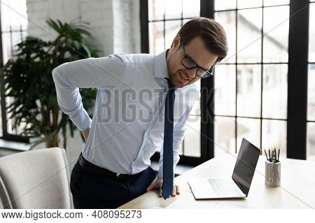 Unhealthy Male Employee Having Back Spasm At Workplace