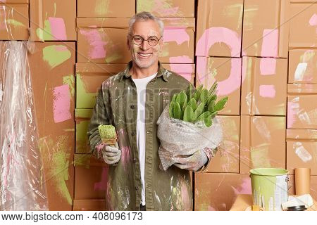 Smiling Grey Haired Man In Casual Clothes Renovates Home Paints Walls In New Apartment Busy With Hou