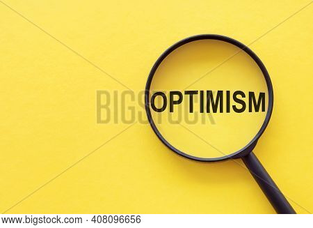 The Word Optimism Is Written On A Magnifying Glass On A Yellow Background.