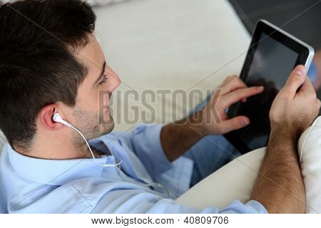 Man sitting in sofa using smartphone and tablet