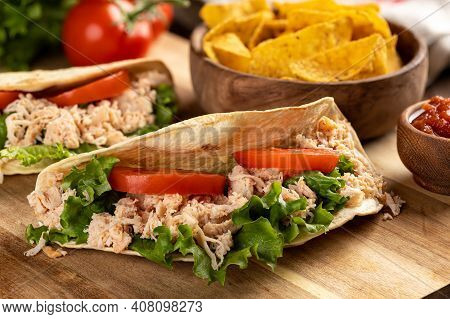 Closeup Of A Chicken Taco With Lettuce And Tomato On A Wooden Cutting Board