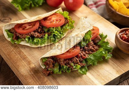 Beef Tacos With Lettuce And Tomato On A Wooden Cutting Board With Tortilla Chips And Salsa In Backgr