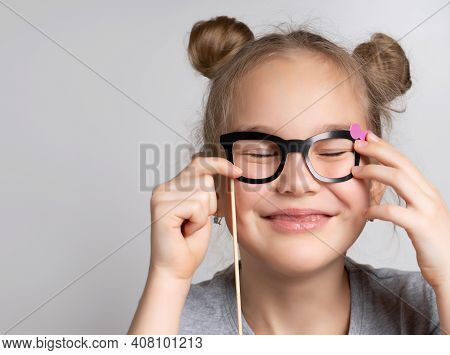 Happy Girl With Eye Closed Wearing Paper Glasses Mask Studio Portrait Shot. Photo Booth Accessory Fo