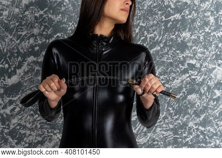 Beautiful Woman Mistress In Latex Bodysuit Holds A Whip In Her Hands.