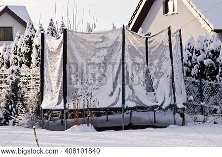 Backyard Trampoline In Winter, Covered With Snow. Off Season In The Garden.