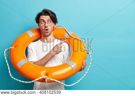 Surprised European Man Ready To Go In Sunny Place On Summer Holidays Carries Inflated Lifebuoy Point