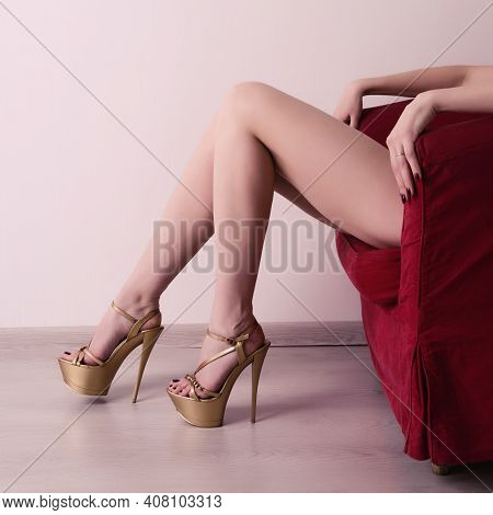 Escort, Prostitute Or Sugar Babe Lying On Red Chair With Long Legs And Sexy Golden High Heels. Prost