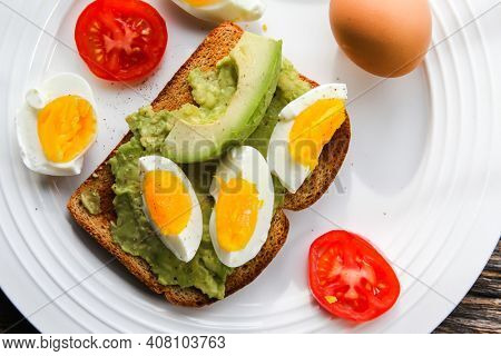 Toast with avocado, tomato slices and eggs on plate from above
