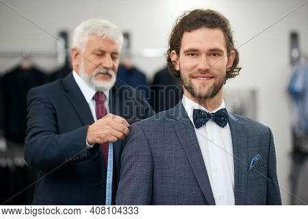 Close Up Of Young Client With Curly Hair In Grey Costume And Bow Tie Choosing Suit In Store. Concept