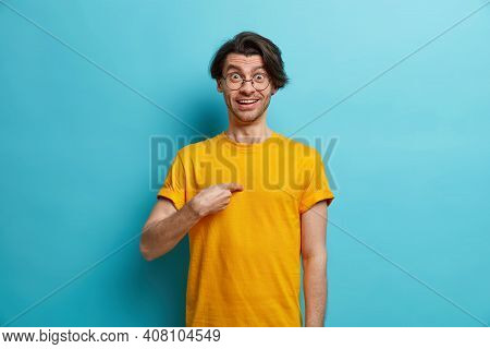 Do You Mean Me. Cheerful Caucasian Man Points At Himself Looks Surprisingly At Camera Surprised Bein