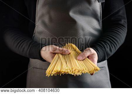 Spaghetti In The Hands Of The Chef Close-up. Italian Long Spaghetti In The Hands Of The Cook On A Da
