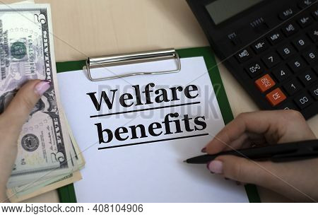 A Woman's Hand Writes In A Notebook The Words Welfare Benefits On The Background Of A Graph, Calcula