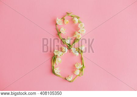 8 March Happy Womens Day Concept. Floral Eight Made Of Spring Flowers On Pink Paper Flat Lay. Stylis