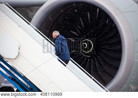 Ukraine, Kyiv - February 15, 2021: A Masked Passenger Climbs The Ladder. Get On The Plane. Airplane