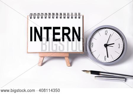 Intern. Text On White Notepad Paper On White Background. Near The Table Clock