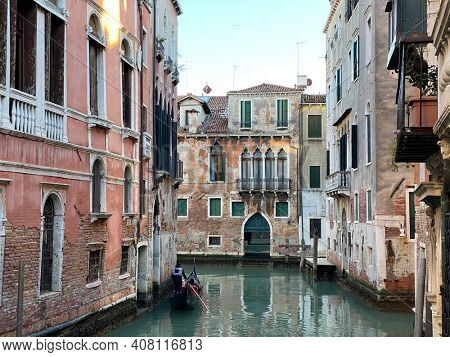 Tourist visiting Venice on a gondola on a small canal street in Venice, Italy