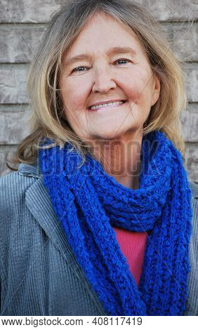 Mature Female Blond Senior Expressions Against A Wall Outdoors.