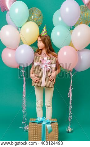 1 White Girl 10 Years Old With A Gift, Pink, Yellow, Blue Balloons For A Holiday On A Green Backgrou