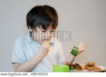 7 Year Old Kid Boy Eating Broccoli, Chicken Nuggets And Roat Potato For Sunday Dinner, Happy Child H
