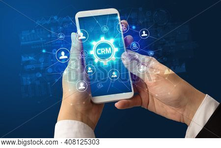 Female hand holding smartphone with CRM abbreviation, modern technology concept