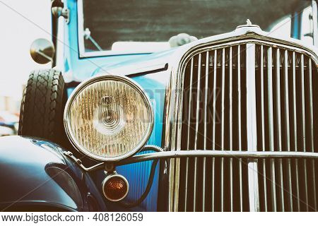 Close Up Of The Front Of An Old Classic Car. Retro Automotive. Detail Of A Front Light. Vintage Blue