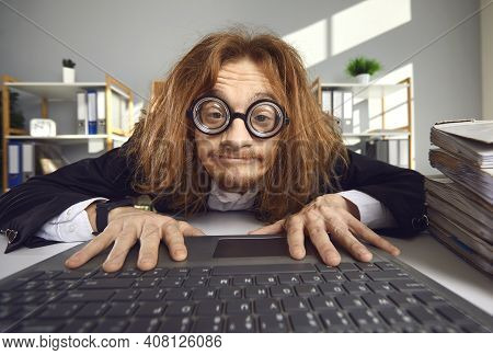 Funny Crazy Looking Nerd In Thick Lens Glasses Sitting In Office And Using Laptop