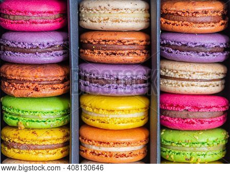 Various Colorful Macarons Or French Macaroons In A Row In A Gift Box, Sweet Meringue-based Confectio