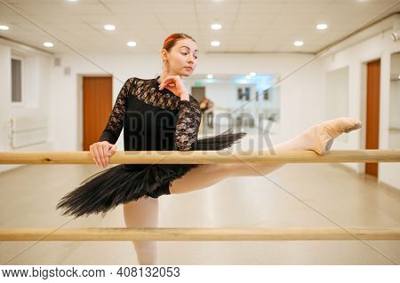 Choreographer poses at the barre, ballet school