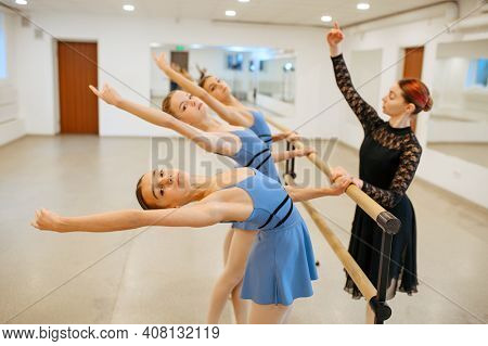 Teacher works with ballerinas at barre in class