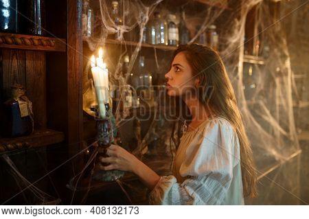 Crazy demonic woman near the shelf with potions
