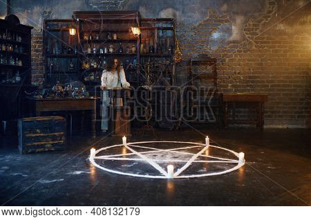 Young demonic woman reads book of spells