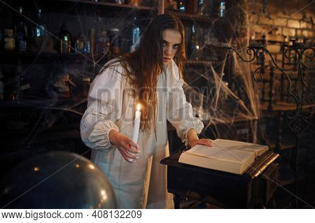 Demonic woman with candle reads book of spells