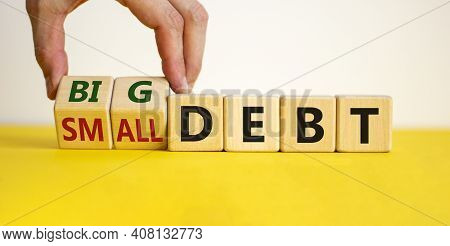 Big Or Small Debt Symbol. Businessman Turns A Wooden Cube And Changes Words 'small Debt' To 'big Deb