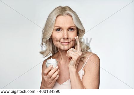 Smiling 50s Middle Aged Mature Woman Putting Tightening Facial Cream On Face Looking At Camera. Anti