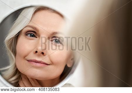 Happy 50s Middle Aged Woman Model Touching Face Skin Looking In Mirror Reflection. Smiling Mature Ol