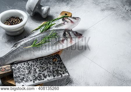 Raw Seabass Fish On A Cutting Board With , Herbs. White Background. Top View. Copy Space