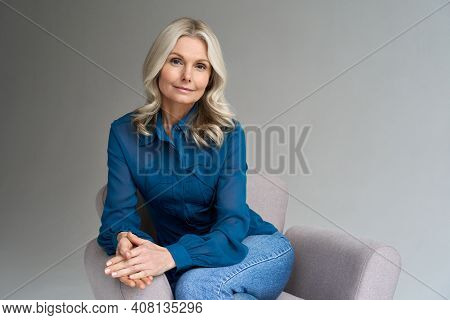 Middle Aged Female Psychotherapist, Counselor Sitting In Chair Alone In Office Looking At Camera. So