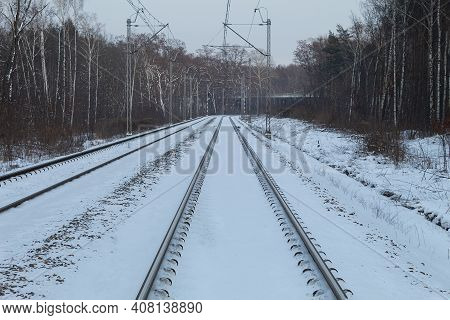 The Rails Are Covered With Snow, View Along The Railway. The Rails In The Winter In The Forest Are C