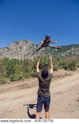 Father Throws Son Up In The Mountains In The Summer In The Crimea