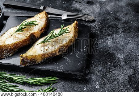 Baked Halibut Fish Steak. Black Background. Top View. Copy Space