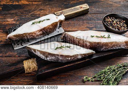Raw Halibut Fish Steak. Dark Wooden Background. Top View