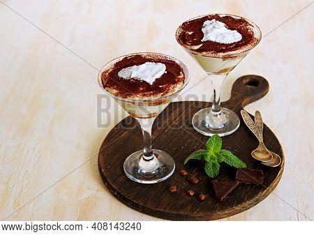 Tiramisu, Dessert With Biscuit Cookies And Mascarpone Cream In Triangular Glasses On A Light Concret