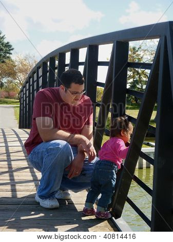 Young father and daughter on bridge.